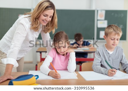 Smiling attractive female teacher checking on a little girls work as she sits alongside a small boy working at a desk in the classroom - stock photo