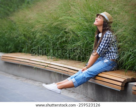 Smiling attractive girl on the bench - stock photo