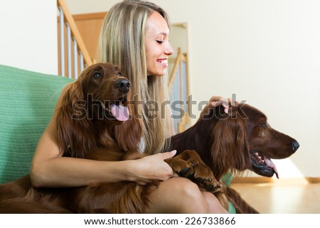 Smiling attractive girl sitting on sofa with two Irish setters. Focus on girl  - stock photo