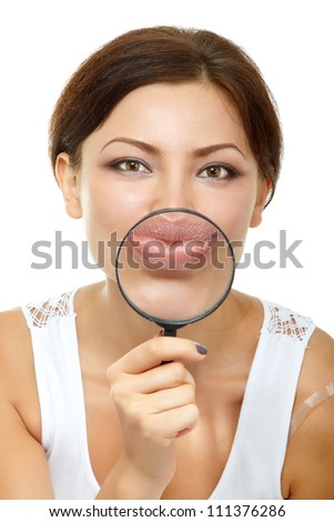 Smiling attractive give kiss through a magnifying glass over white background - stock photo