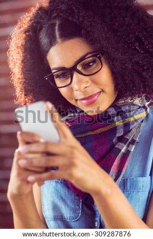 Smiling attractive hipster texting against red brick background - stock photo