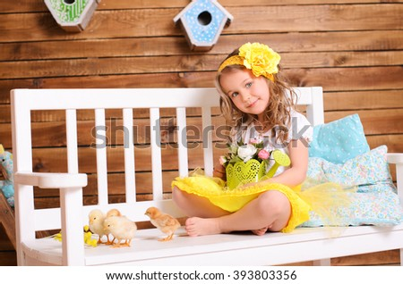 smiling attractive little girl in white and yellow with wavy hair playing with alive chickens and watering pot on bench indoors - stock photo