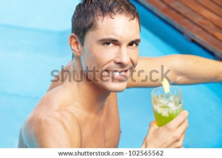 Smiling attractive man with cocktail drink in swimming pool - stock photo