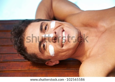 Smiling attractive man with sunscreen on nose and cheeks - stock photo