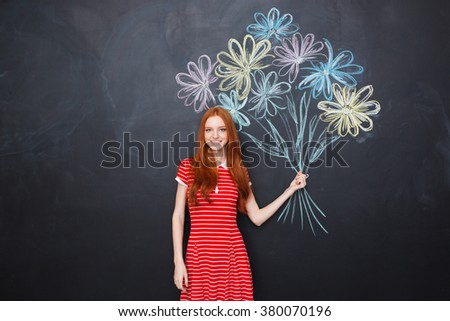 Smiling attractive redhead young woman standing and holding bouquet of drawn flowers over blackboard background - stock photo