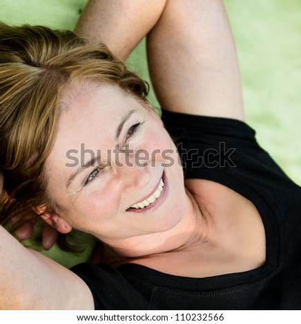 Smiling attractive senior woman lying outdoor on rug - stock photo