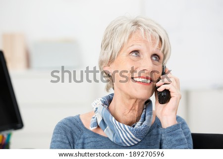 Smiling attractive senior women using a mobile phone looking thoughtfully into the air as she listens to the conversation - stock photo