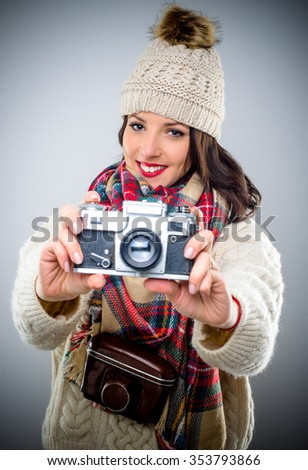 Smiling attractive stylish female photographer in winter fashion holding a vintage camera pointed at the camera with the leather case around her neck, over grey - stock photo