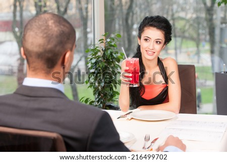 Smiling attractive woman drinking juice with straw. back view of man listening to girl at lunch break - stock photo