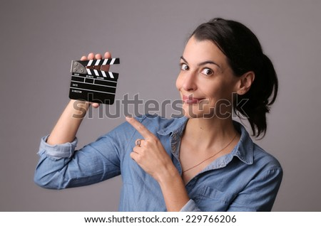 Smiling attractive woman in jeans shirt holding a production set clapper with gray studio background - stock photo