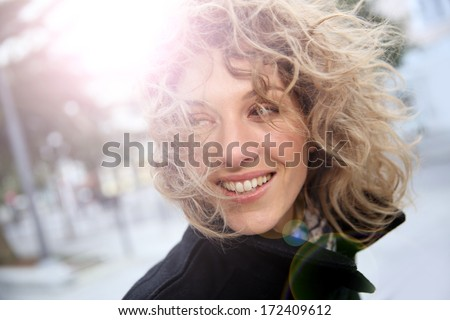 Smiling attractive woman in town in winter time - stock photo