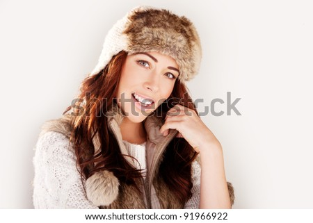 Smiling attractive woman in winter fur hat close-up studio portrait on white - stock photo