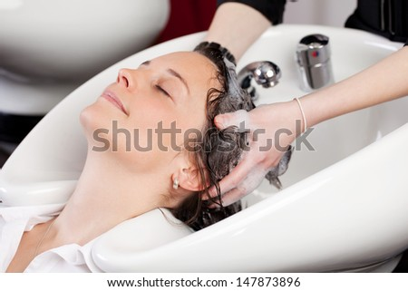 Smiling attractive woman with her eyes closed in enjoyment having a hair shampoo at the hair salon - stock photo