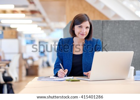 Smiling attractive young businesswoman working at her desk - stock photo