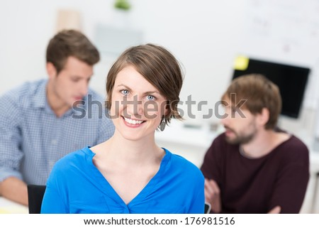 Smiling attractive young female office worker standing looking at the camera in front of two male business colleagues engaged in a discussion