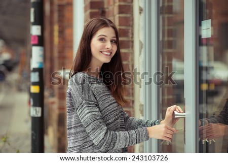 Smiling attractive young female student entering a commercial building looking at the camera as she pushes open the glass door - stock photo