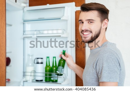Smiling attractive young man taking bottle of beer from refrigerator on the kitchen  - stock photo