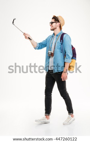 Smiling attractive young tourist with backpack walking and using mobile phone on selphie stick over white background - stock photo