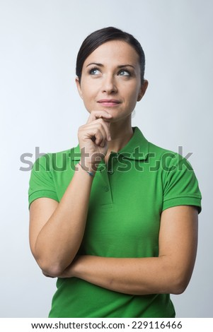 Smiling attractive young woman in green t-shirt with hand on chin. - stock photo