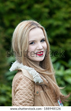 Smiling attractive young woman with long blond hair standing sideways outdoors in a lush green garden turning her head to smile at the camera - stock photo
