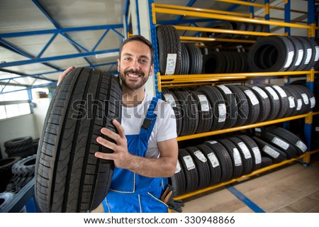 smiling auto mechanic carrying tire in tire store - stock photo