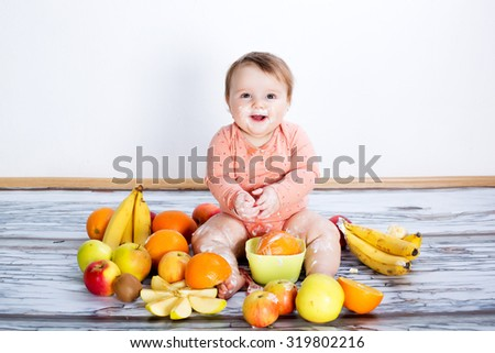 Smiling baby and many kinds of fruit and bowl with yoghurt - stock photo