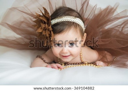 Smiling baby ballerina in brown tutu with a pearl necklace - stock photo