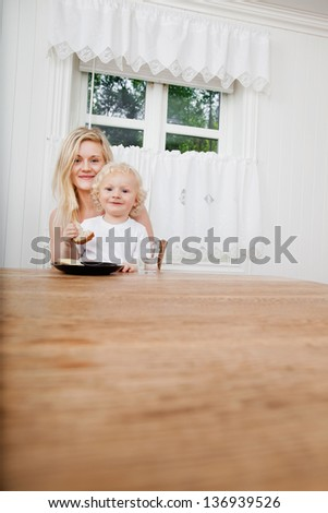 Smiling baby boy eating bread while sitting on lap of mother - stock photo