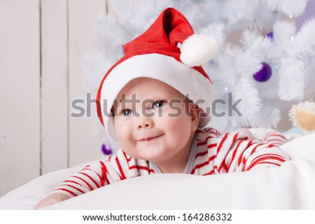 Smiling baby boy in Santa`s hat on the soft white pillow under the decorated Christmas tree - stock photo