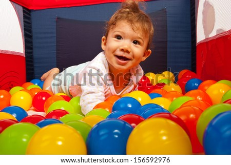 Smiling baby boy lying in colorful balls inside a playpen - stock photo