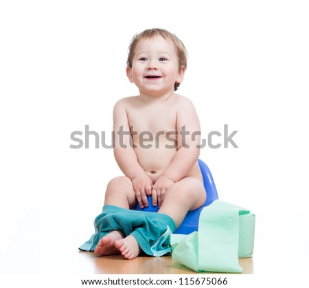 smiling baby boy sitting on chamber pot with toilet paper roll - stock photo