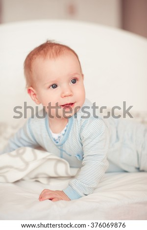 Smiling baby boy wake up in bed in room. Wearing pajamas. Looking away. Good morning.