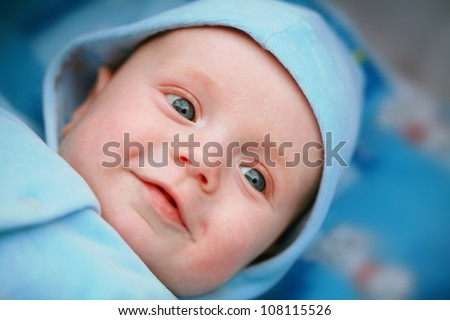 Smiling baby boy with big blue eyes close up - stock photo