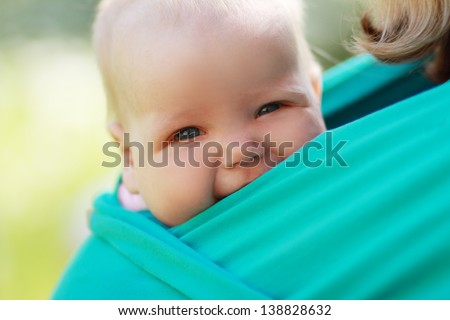 Smiling baby closed to mom in sling outdoor - stock photo