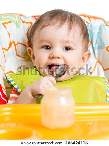 smiling baby eating food with spoon - stock photo