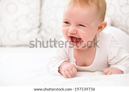 Smiling Baby Girl are Lying in the Bed - stock photo