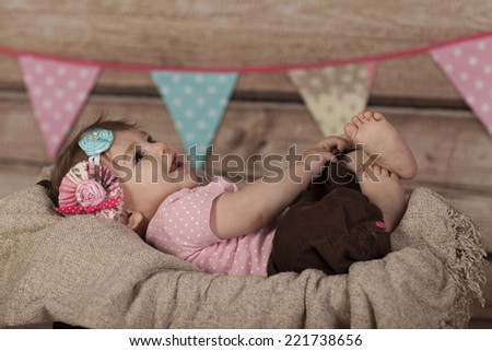 Smiling Baby Girl lying in basket focus on feet - stock photo