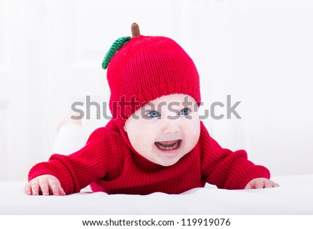 Smiling baby girl playing on her tummy wearing a red apple hat - stock photo