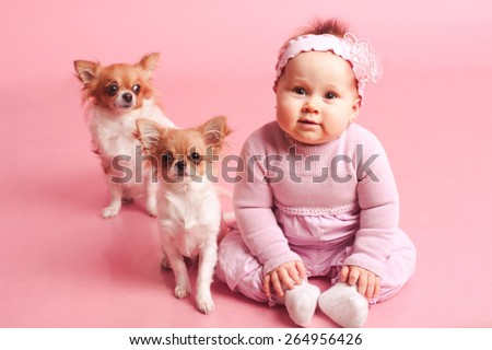 Smiling baby girl playing with funny little dogs in room over pink. Looking at camera. Laughing. Having fun. Childhood. - stock photo