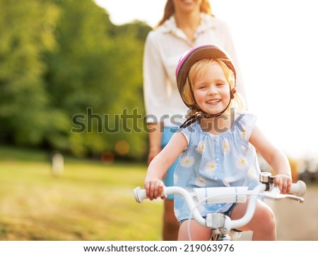 Smiling baby girl riding bicycle - stock photo
