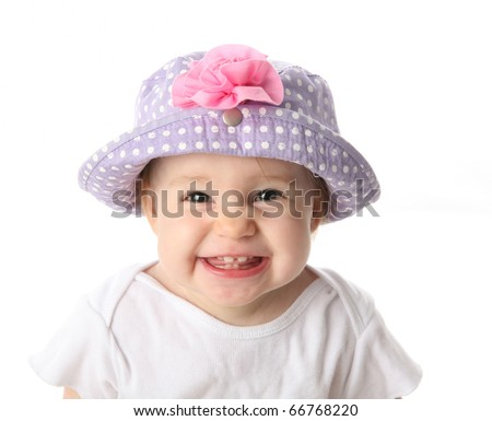 Smiling baby girl showing teeth wearing a purple polka dot hat with pink flower isolated on white background - stock photo