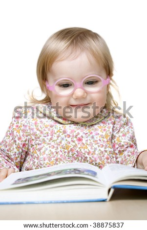 Smiling baby girl with glasses reading book