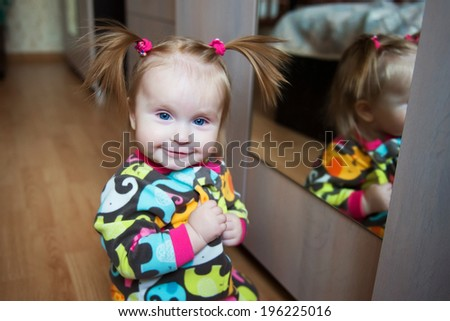 smiling baby girl with tails at home