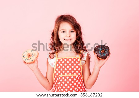 Smiling baby girl 4-5 year old holding two donuts in hands over pink. Looking at camera. Childhood. Tasty cakes. Cooking. - stock photo