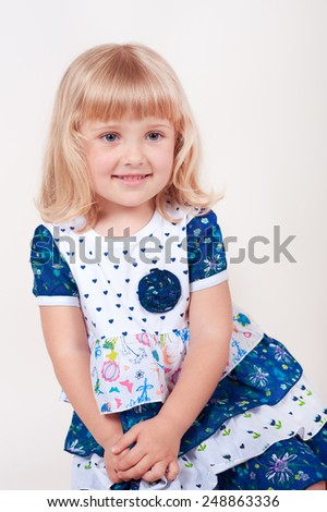 Smiling baby girl 3-4 years old posing over white in room. Childhood. - stock photo