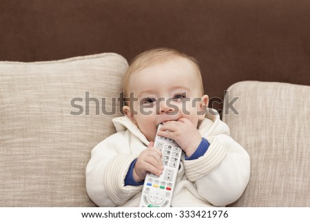 Smiling baby holding a remote control tv - stock photo