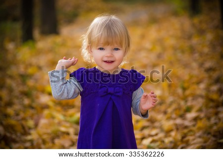 smiling baby in autumn forest with yellow leaves playing and dancing - stock photo