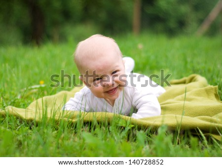 Smiling baby lying in a park - stock photo