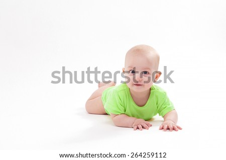 smiling baby lying on his stomach and looking at the camera, picture with depth of field