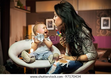 Smiling baby playing with his mum - stock photo